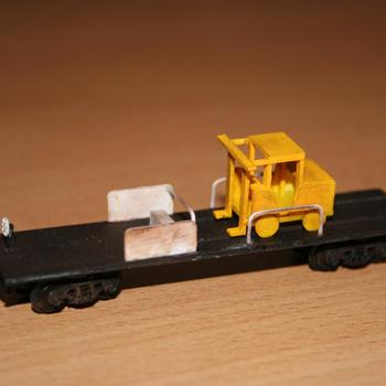 Weathered VZCA flat wagon with sleeper discharge machine loaded on top